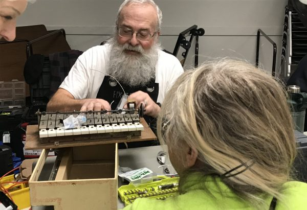 Fixer working with guest to repair toy piano