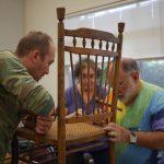 3 people repairing a chair